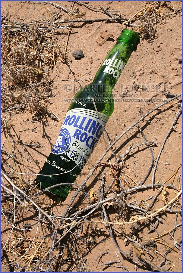 Photo of beer bottle in desert sand by Tucson photographer Martha Lochert